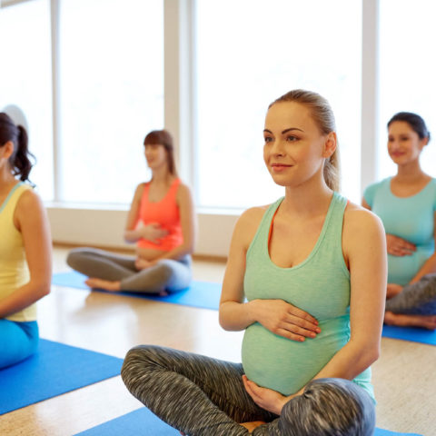 pregnancy, fitness and healthy lifestyle concept - group of happy pregnant women exercising in lotus pose at gym yoga