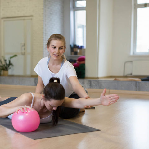 Personal trainer, pilates. Two women works with small fit ball, one helps another to do exersice for her back. Fitness studio, selected focus